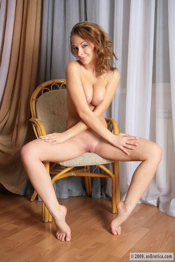 Petite blond Olivia with firm tits posing nude on the chair