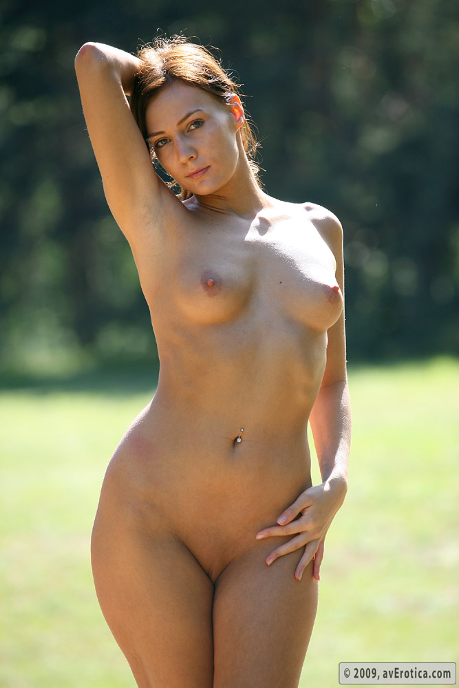 Masha posing naked in the field spreading her pussy lips