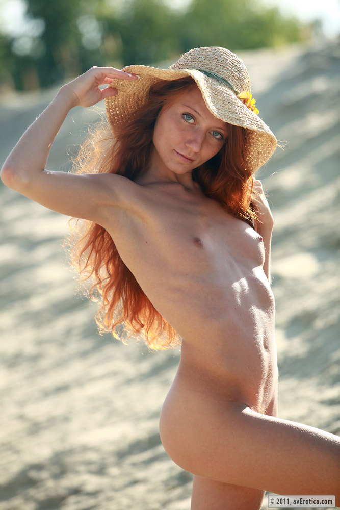 Very petite redhead with small perky tits laying naked on the sand