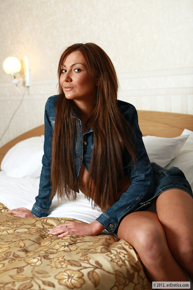 Sexy tanned babe posing in denim jacket